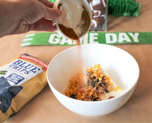adding spices to a football party dip